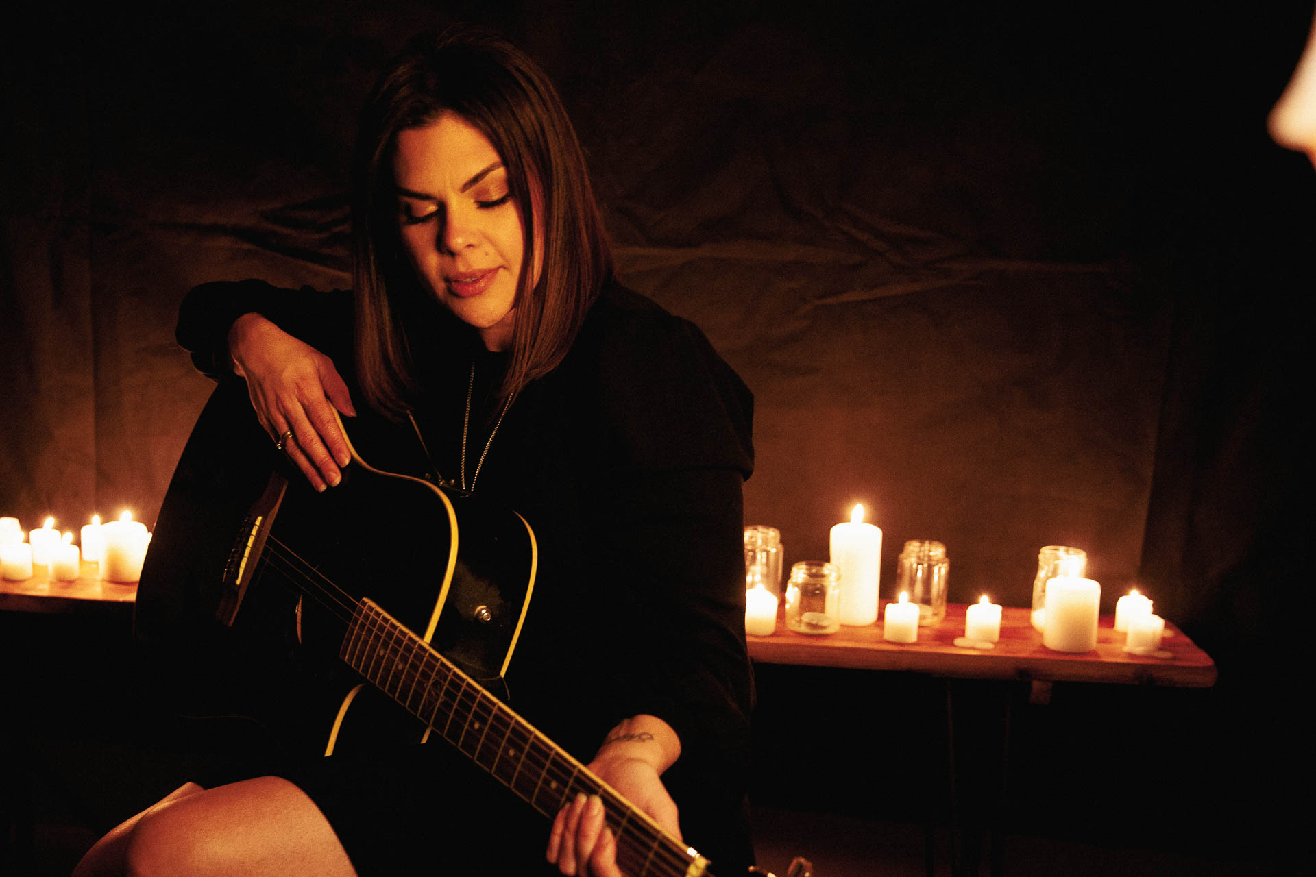 Portrait of Jessica Wishart with a guitar and candles in the background